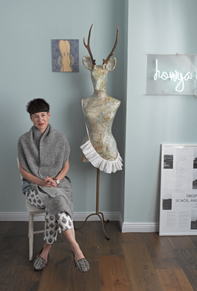 """Aoibheann wears a woolen scarf, of her own design, and sits among several pieces from her art collection. She had the """"howya now loveen"""" neon sign made in Hong Kong."""