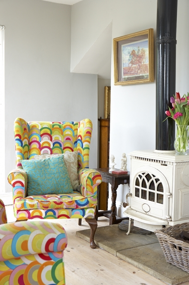 The chairs were inherited and covered in colourful material from Ikea. The original stove was painted white, and the floorboards were sanded and white washed. The framed picture is by painter John Jobson.