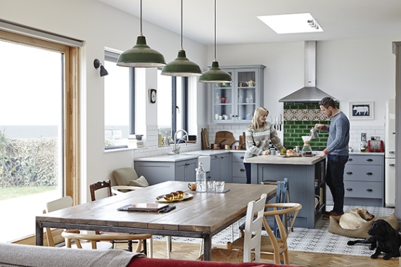The couple relax in their kitchen by Rhatigan & Hick. The Carrera marble worktop is from Lamont Stone, Coleraine. The range cooker is by Mercury. The wall and floor tiles are by Fired Earth. The dining table is from metroretro.co.uk