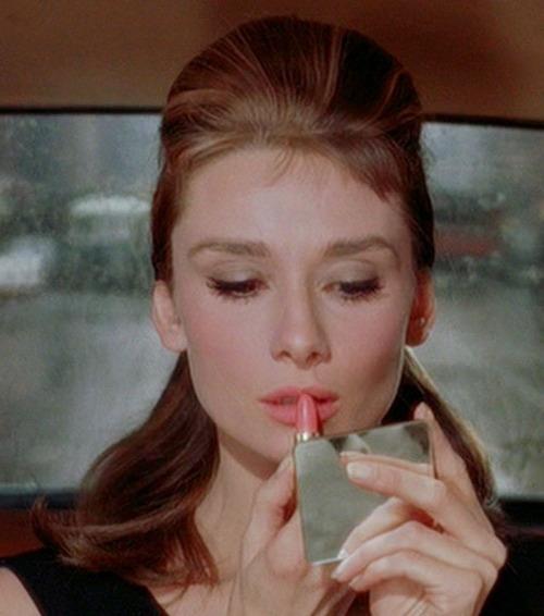 Audrey Hepburn applying lipstick