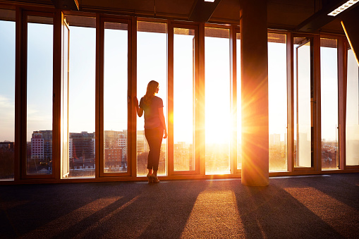 Businesswoman looks across city at sunrise