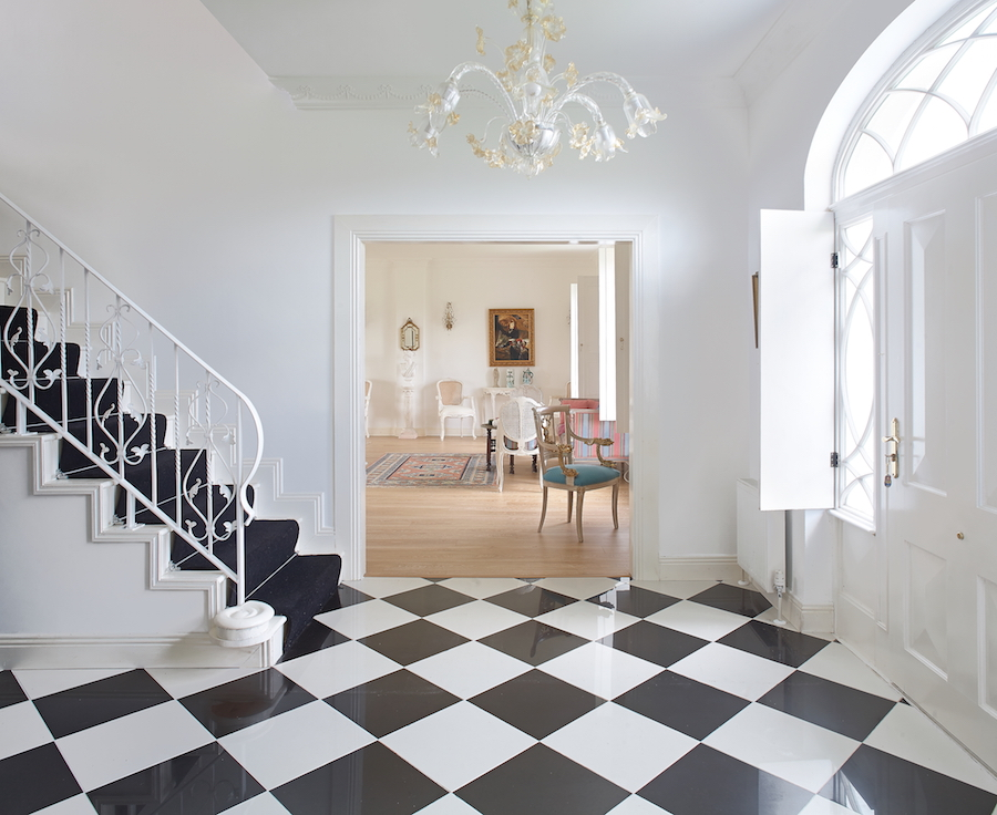 """""""We chose the black and white tiles look for the entrance hall,"""" says owner Ginger. The tiles were sourced in Right Price Tiles in Castlebar, while Ginger spotted the hand-blown Venetian glass chandelier in a closing-down sale in Galway. The wrought-iron balustrade on the stairs was commissioned from Paul Lyons in Bó Steel, Loughrea."""