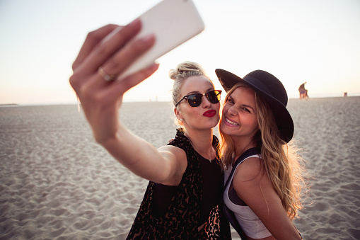 Female friends photographing themselves on smartphone