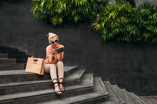 Caucasian woman using digital tablet on stairs