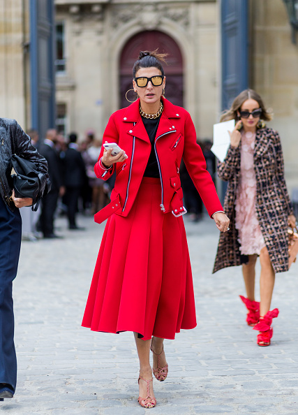Giovanna Battaglia wears a red skirt and red jacket outside of Dior