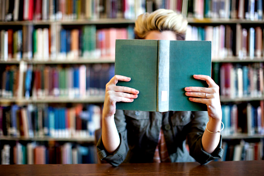 Woman reading book in library